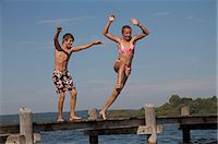 Young friends jumping into water from pier Stock Photo - Premium Royalty-Freenull, Code: 618-06405685