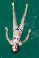 Girl floating in sea, high angle view Stock Photo - Premium Royalty-Freenull, Code: 618-06405693