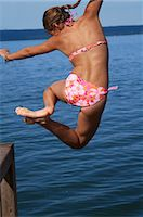 Girl jumping into sea, rear view Stock Photo - Premium Royalty-Freenull, Code: 618-06405694
