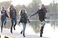 Girls skipping together on lake pier Stock Photo - Premium Royalty-Freenull, Code: 618-06405866
