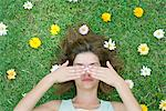 Woman lying on grass surrounded by flowers with hands covering eyes Stock Photo - Premium Royalty-Free, Artist: Uwe Umsttter, Code: 633-06406456