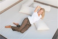 Young woman relaxing on bed Stock Photo - Premium Royalty-Freenull, Code: 633-06406797