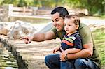 Happy Hispanic Father Points with Mixed Race Son at the Park Pond. Stock Photo - Royalty-Free, Artist: Feverpitched                  , Code: 400-06417109