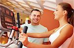 Portrait of pretty girl training in gym with her trainer near by Stock Photo - Royalty-Free, Artist: pressmaster                   , Code: 400-06417282