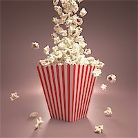 Dropping popcorn in striped classic package. Stock Photo - Royalty-Freenull, Code: 400-06421053