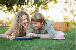 Playful Loving Couple Using a Touch Pad Computer at Their Picnic Outside. Stock Photo - Royalty-Free, Artist: Feverpitched                  , Code: 400-06425438