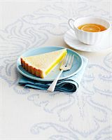 Slice of Lemon Tart and Fork on Blue Plate with Cup and Saucer of Herbal Tea on Tablecloth in Studio Stock Photo - Premium Royalty-Freenull, Code: 600-06431335