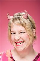 Portrait of Woman Wearing Devil Horns and Scowling Stock Photo - Premium Royalty-Freenull, Code: 600-06431389