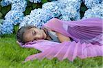Girl Wearing Fairy Wings Lying Down Outside in Flower Garden