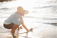 Woman playing in waves at beach Stock Photo - Premium Royalty-Freenull, Code: 649-06432380