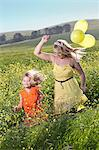 Sisters playing in field of flowers Stock Photo - Premium Royalty-Free, Artist: Ikonica, Code: 649-06432411