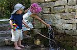 Children playing at water spout in wall Stock Photo - Premium Royalty-Free, Artist: David & Micha Sheldon, Code: 649-06432426