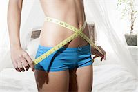 Woman measuring her belly with tape Stock Photo - Premium Royalty-Freenull, Code: 649-06432477
