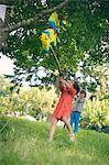 Girl swinging at pinata at party Stock Photo - Premium Royalty-Free, Artist: Blend Images, Code: 649-06432523