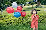 Girl holding bunch of balloons outdoors Stock Photo - Premium Royalty-Free, Artist: R. Ian Lloyd, Code: 649-06432531