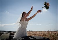 Newlywed bride tossing bouquet from car Stock Photo - Premium Royalty-Freenull, Code: 649-06432543