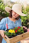 Woman carrying wooden box of flowers Stock Photo - Premium Royalty-Free, Artist: Blend Images, Code: 649-06432655