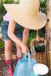 Girl filling up watering can at spout Stock Photo - Premium Royalty-Free, Artist: Blend Images, Code: 649-06432678