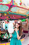 Woman eating cotton candy at fair Stock Photo - Premium Royalty-Free, Artist: Westend61, Code: 649-06432909