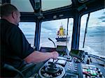Worker driving tugboat in wheelhouse Stock Photo - Premium Royalty-Free, Artist: John Lee, Code: 649-06433063