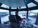 Worker driving tugboat in wheelhouse Stock Photo - Premium Royalty-Free, Artist: Cultura RM, Code: 649-06433065