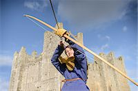 Student in period dress shooting arrow Stock Photo - Premium Royalty-Freenull, Code: 649-06433138