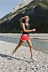 Woman jogging on gravel river bank Stock Photo - Premium Royalty-Free, Artist: ableimages, Code: 649-06433299