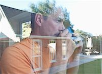 Man having coffee reflected in window Stock Photo - Premium Royalty-Freenull, Code: 649-06433539