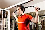 Man using exercise equipment at gym Stock Photo - Premium Royalty-Free, Artist: Westend61, Code: 649-06433555