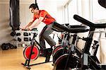 Man using stationary bicycle at gym