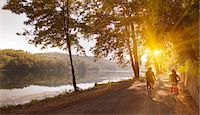 Couple riding bicycles by river bank Stock Photo - Premium Royalty-Freenull, Code: 649-06433680