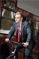 Young businessman riding bicycle by bus Stock Photo - Premium Royalty-Freenull, Code: 693-06435823