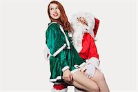 Happy young woman sitting on Santa's laps against gray background Stock Photo - Premium Royalty-Freenull, Code: 693-06435905
