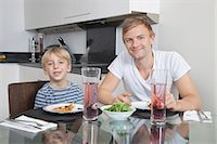 Portrait of father and son smiling at breakfast table Stock Photo - Premium Royalty-Freenull, Code: 693-06435989