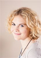 Close-up Portrait of Blond, Teenage Girl with Curly Hair, Smiling at Camera, Studio Shot on White Background Stock Photo - Premium Royalty-Freenull, Code: 600-06438965