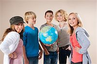 Portrait of Group of Teenage Boys and Girls Holding World Globe, Smiling and Looking at Camera, Studio Shot on White Background Stock Photo - Premium Royalty-Freenull, Code: 600-06438968