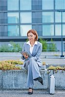 Businesswoman Sitting Outside in front of Office Building using Tablet PC, Niederrad, Frankfurt, Germany Stock Photo - Premium Royalty-Freenull, Code: 600-06438975