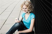 Portrait of Teenage Girl Smiling, Sitting on Sidewalk using Cellphone, Mannheim, Germany Stock Photo - Premium Royalty-Freenull, Code: 600-06438976