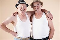 Portrait of Two Senior Man wearing Undershirts and Hats while Smoking Cigars with Arms around Shoulders, Studio Shot on Beige Background Stock Photo - Premium Royalty-Freenull, Code: 600-06438991