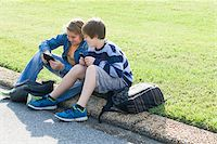 Two Boys Sitting on Curb with Handheld Electronics Stock Photo - Premium Rights-Managednull, Code: 700-06439141