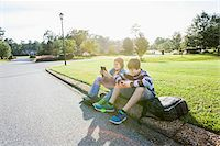 Two Boys Sitting on Neighbourhood Curb with Handheld Electronics Stock Photo - Premium Rights-Managednull, Code: 700-06439142