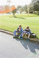 Two Boys Sitting on Neighbourhood Curb with Handheld Electronics Stock Photo - Premium Rights-Managednull, Code: 700-06439143