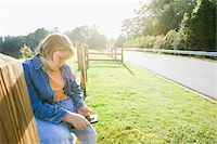Boy Sitting Outdoors on Roadside Fence with Tablet Computer Stock Photo - Premium Rights-Managednull, Code: 700-06439148