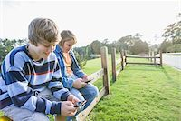 Two Boys with Handheld Electronics Sitting on Roadside Fence Stock Photo - Premium Rights-Managednull, Code: 700-06439150