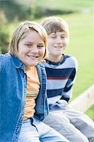Portrait of Two Boys Sitting Outdoors on Fence Stock Photo - Premium Rights-Managednull, Code: 700-06439151