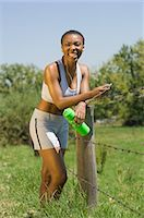 Female Jogger Resting by Fence Stock Photo - Premium Rights-Managednull, Code: 873-06441196