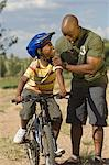 Father Helping Son Ride Bike Stock Photo - Premium Rights-Managed, Artist: GreatStock, Code: 873-06441212