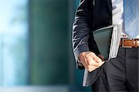 Businessman carrying tablet PC and newspaper under his arm Stock Photo - Premium Rights-Managednull, Code: 853-06441629