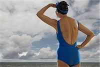 Senior woman wearing swimsuit looking towards sea, shielding eyes Stock Photo - Premium Royalty-Freenull, Code: 614-06442312
