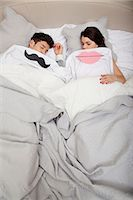 Couple in bed with lips and moustache Stock Photo - Premium Royalty-Freenull, Code: 614-06442402